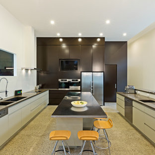 Photo of a contemporary kitchen in Melbourne with a double-bowl sink, stainless steel benchtops, concrete floors and multiple islands.