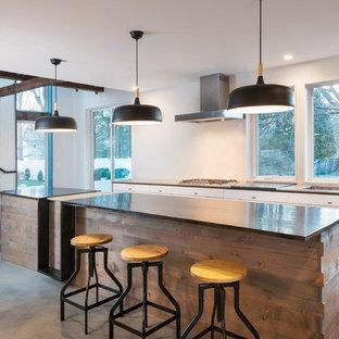 Industrial Küche mit Unterbauwaschbecken, flächenbündigen Schrankfronten, weißen Schränken, Rückwand-Fenster, Betonboden, Kücheninsel, grauem Boden und schwarzer Arbeitsplatte in Providence