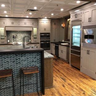 ニューヨークの大きいおしゃれなキッチン (アンダーカウンターシンク、フラットパネル扉のキャビネット、グレーのキャビネット、木材カウンター、緑のキッチンパネル、磁器タイルのキッチンパネル、シルバーの調理設備、無垢フローリング、茶色い床、茶色いキッチンカウンター) の写真
