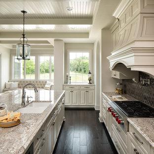 Klassische Küche mit Unterbauwaschbecken, Schrankfronten mit vertiefter Füllung, weißen Schränken, Küchenrückwand in Metallic, Rückwand aus Metallfliesen, Küchengeräten aus Edelstahl, dunklem Holzboden und Kücheninsel in Minneapolis