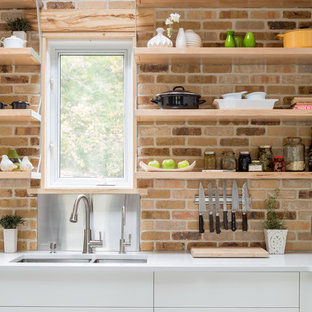 Design ideas for a mid-sized industrial u-shaped eat-in kitchen in Toronto with a double-bowl sink, flat-panel cabinets, white cabinets, quartz benchtops, multi-coloured splashback, stone tile splashback, stainless steel appliances, ceramic floors and no island.
