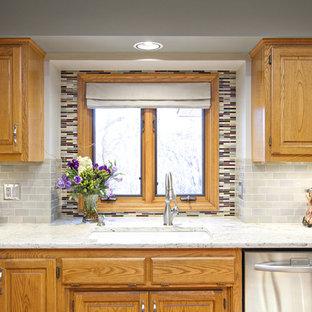 Идея дизайна: кухня в стиле фьюжн с врезной раковиной, фасадами с выступающей филенкой, фасадами цвета дерева среднего тона, серым фартуком, фартуком из плитки кабанчик и техникой из нержавеющей стали