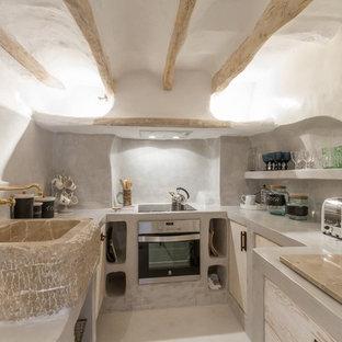 Ejemplo de cocina en U, mediterránea, pequeña, cerrada, con armarios con paneles lisos, puertas de armario con efecto envejecido, encimera de cemento, electrodomésticos de acero inoxidable, suelo blanco, encimeras grises, salpicadero verde y fregadero sobremueble