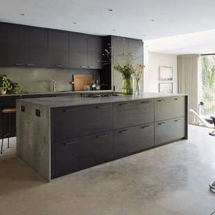 Inspiration for a large contemporary galley kitchen/diner in Sussex with flat-panel cabinets, concrete worktops, grey splashback, stone slab splashback, black appliances, concrete flooring, an island, grey floors, grey worktops, a submerged sink and black cabinets.