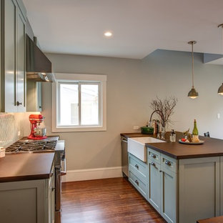 Design ideas for a small transitional galley eat-in kitchen in San Francisco with a farmhouse sink, shaker cabinets, green cabinets, concrete benchtops, green splashback, ceramic splashback, stainless steel appliances, dark hardwood floors and a peninsula.