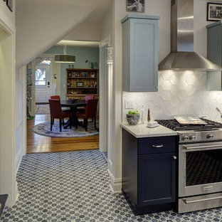 Mid-sized eclectic u-shaped kitchen in New York with a single-bowl sink, shaker cabinets, blue cabinets, quartz benchtops, white splashback, ceramic splashback, stainless steel appliances, porcelain floors, a peninsula, blue floor and multi-coloured benchtop.