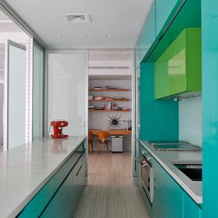 Imagen de cocina de galera, moderna, con electrodomésticos de acero inoxidable, armarios con paneles lisos y puertas de armario azules
