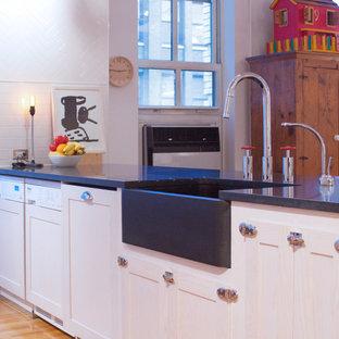ニューヨークの大きいインダストリアルスタイルのおしゃれなキッチン (エプロンフロントシンク、シェーカースタイル扉のキャビネット、御影石カウンター、白いキッチンパネル、黒いキッチンカウンター、ヴィンテージ仕上げキャビネット、サブウェイタイルのキッチンパネル、シルバーの調理設備の、淡色無垢フローリング、ベージュの床) の写真