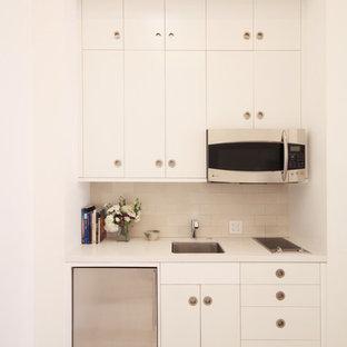 Idéer för att renovera ett mellanstort funkis linjärt kök med öppen planlösning, med en undermonterad diskho, släta luckor, vita skåp, bänkskiva i kvarts, beige stänkskydd, stänkskydd i tunnelbanekakel, rostfria vitvaror och målat trägolv