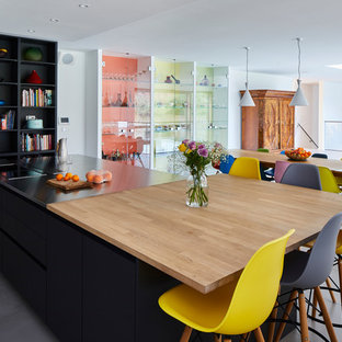 This is an example of a large contemporary single-wall open plan kitchen with flat-panel cabinets, an island, grey floors, black cabinets, stainless steel worktops, yellow splashback, glass sheet splashback, stainless steel appliances and ceramic flooring.