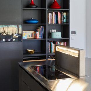 Modelo de cocina lineal, minimalista, grande, abierta, con puertas de armario negras, encimera de acero inoxidable, salpicadero amarillo, salpicadero de vidrio templado, electrodomésticos de acero inoxidable, suelo de baldosas de cerámica, una isla y suelo gris