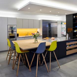 広いモダンスタイルのおしゃれなキッチン (黄色いキッチンパネル、シルバーの調理設備、グレーの床、黒いキャビネット、ステンレスカウンター、ガラス板のキッチンパネル、セラミックタイルの床) の写真