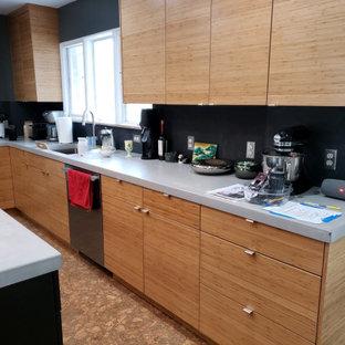 Exempel på ett 60 tals grå grått kök, med släta luckor, skåp i mellenmörkt trä, bänkskiva i betong, svart stänkskydd, stänkskydd i skiffer, rostfria vitvaror och en köksö