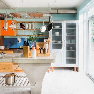 Foto de cocina de galera, ecléctica, con armarios con paneles empotrados, puertas de armario naranjas, salpicadero azul, salpicadero de vidrio templado, una isla, suelo blanco y encimeras beige