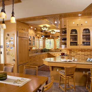 Craftsman eat-in kitchen pictures - Example of an arts and crafts u-shaped slate floor eat-in kitchen design in Minneapolis with an undermount sink, flat-panel cabinets, light wood cabinets, brown backsplash, paneled appliances and a peninsula