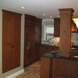 Large classic u-shaped kitchen pantry in New York with a belfast sink, medium wood cabinets, granite worktops, beige splashback, porcelain splashback, stainless steel appliances, ceramic flooring and an island.