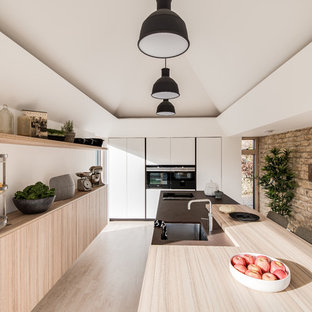 This is an example of a medium sized contemporary single-wall open plan kitchen in Gloucestershire with an integrated sink, flat-panel cabinets, white cabinets, composite countertops, black appliances, light hardwood flooring, a breakfast bar, beige floors and brown worktops.