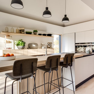 Photo of a medium sized contemporary single-wall kitchen in Gloucestershire with a submerged sink, flat-panel cabinets, white cabinets, black appliances, light hardwood flooring, an island, multicoloured worktops and beige floors.