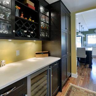Idée de décoration pour une arrière-cuisine linéaire craftsman de taille moyenne avec un placard à porte shaker, des portes de placard en bois sombre, un plan de travail en quartz modifié, un électroménager en acier inoxydable, un sol en bois brun et une crédence jaune.