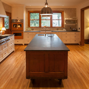 Photo of a large arts and crafts separate kitchen in Portland with a farmhouse sink, open cabinets, white cabinets, beige splashback, terra-cotta splashback, panelled appliances, medium hardwood floors and with island.