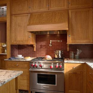 Geschlossene Urige Küche in U-Form mit Unterbauwaschbecken, Schrankfronten im Shaker-Stil, hellbraunen Holzschränken, Granit-Arbeitsplatte, Küchenrückwand in Rot, Rückwand aus Metrofliesen, Küchengeräten aus Edelstahl, Schieferboden und Kücheninsel in Minneapolis