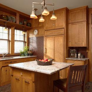 ミネアポリスのおしゃれなキッチン (アンダーカウンターシンク、シェーカースタイル扉のキャビネット、中間色木目調キャビネット、御影石カウンター、赤いキッチンパネル、サブウェイタイルのキッチンパネル、パネルと同色の調理設備、スレートの床) の写真