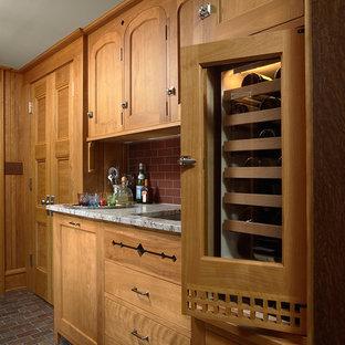 ミネアポリスのトラディショナルスタイルのおしゃれなキッチン (アンダーカウンターシンク、シェーカースタイル扉のキャビネット、中間色木目調キャビネット、御影石カウンター、赤いキッチンパネル、サブウェイタイルのキッチンパネル、パネルと同色の調理設備、スレートの床) の写真