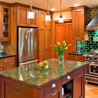 Photo of a large traditional u-shaped enclosed kitchen in Other with granite worktops, green splashback, recessed-panel cabinets, medium wood cabinets, stainless steel appliances, cork flooring and an island.