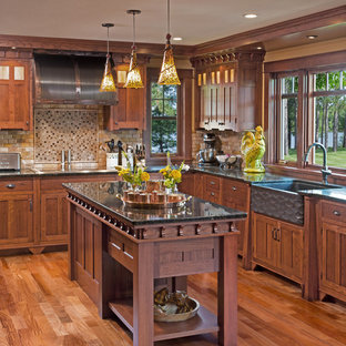 Large craftsman eat-in kitchen designs - Large arts and crafts u-shaped dark wood floor eat-in kitchen photo in Milwaukee with a farmhouse sink, recessed-panel cabinets, medium tone wood cabinets, granite countertops, brown backsplash, stone tile backsplash, paneled appliances and two islands