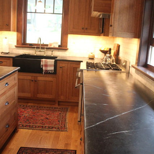 Mid-sized craftsman eat-in kitchen appliance - Inspiration for a mid-sized craftsman l-shaped medium tone wood floor eat-in kitchen remodel in Other with a farmhouse sink, shaker cabinets, medium tone wood cabinets, soapstone countertops, white backsplash, subway tile backsplash, stainless steel appliances and an island