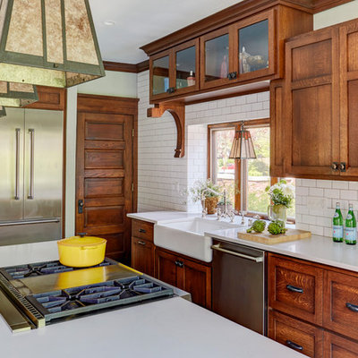 Mid-sized arts and crafts medium tone wood floor and brown floor kitchen photo in Milwaukee with a farmhouse sink, shaker cabinets, medium tone wood cabinets, quartz countertops, white backsplash, subway tile backsplash, stainless steel appliances, an island and white countertops