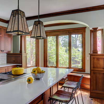 Inspiration for a mid-sized craftsman medium tone wood floor and brown floor kitchen remodel in Milwaukee with a farmhouse sink, shaker cabinets, medium tone wood cabinets, quartz countertops, white backsplash, subway tile backsplash, stainless steel appliances, an island and white countertops