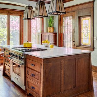 ミルウォーキーの中くらいのおしゃれなアイランドキッチン (エプロンフロントシンク、シェーカースタイル扉のキャビネット、中間色木目調キャビネット、クオーツストーンカウンター、白いキッチンパネル、サブウェイタイルのキッチンパネル、シルバーの調理設備、無垢フローリング、茶色い床、白いキッチンカウンター) の写真