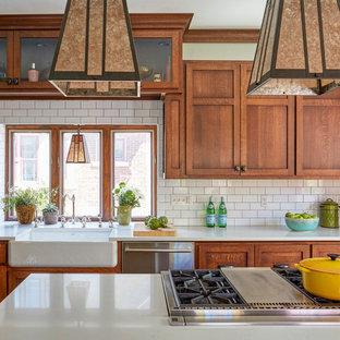 Cette image montre une cuisine craftsman de taille moyenne avec un évier de ferme, un placard à porte shaker, des portes de placard en bois brun, un plan de travail en quartz modifié, une crédence blanche, une crédence en carrelage métro, un électroménager en acier inoxydable, un sol en bois brun, un îlot central, un sol marron et un plan de travail blanc.