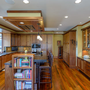 Large craftsman kitchen photos - Large arts and crafts u-shaped medium tone wood floor kitchen photo in Minneapolis with a double-bowl sink, solid surface countertops, paneled appliances, an island and brown backsplash