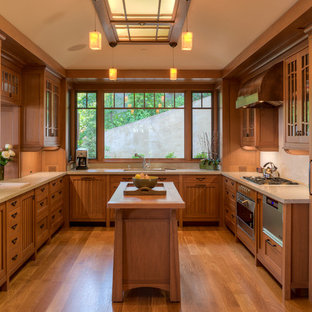 Inspiration for an arts and crafts u-shaped kitchen in San Francisco with glass-front cabinets, medium wood cabinets, beige splashback, panelled appliances, medium hardwood floors and with island.
