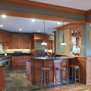 Diseño de cocina comedor en U, de estilo americano, grande, con armarios estilo shaker, electrodomésticos de acero inoxidable, fregadero sobremueble, puertas de armario de madera en tonos medios, encimera de cuarzo compacto, suelo de pizarra y península