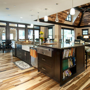 Craftsman eat-in kitchen inspiration - Inspiration for a craftsman galley light wood floor eat-in kitchen remodel in Dallas with a farmhouse sink, shaker cabinets, dark wood cabinets, granite countertops, multicolored backsplash, glass sheet backsplash, stainless steel appliances and an island