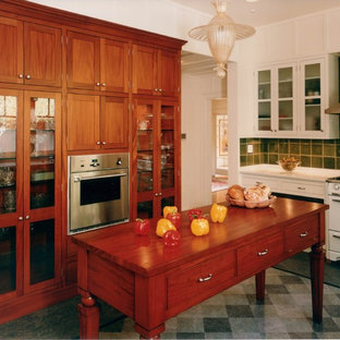Mediterranean kitchen ideas - Tuscan gray floor kitchen photo in San Francisco with glass-front cabinets, medium tone wood cabinets, green backsplash and white appliances