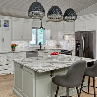 Foto på ett mellanstort vintage grå kök, med vita skåp, bänkskiva i kvartsit, vitt stänkskydd, stänkskydd i marmor, svarta vitvaror, vinylgolv, en köksö, brunt golv, en undermonterad diskho och skåp i shakerstil