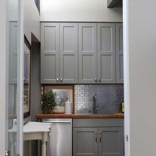 Zweizeilige, Mittelgroße Mid-Century Küche mit Vorratsschrank, Unterbauwaschbecken, Arbeitsplatte aus Holz, braunem Holzboden und Kücheninsel in Sonstige