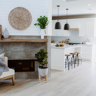 Mid-sized beach style l-shaped open plan kitchen in San Diego with an undermount sink, shaker cabinets, white cabinets, quartz benchtops, white splashback, ceramic splashback, stainless steel appliances, ceramic floors, with island and brown floor.