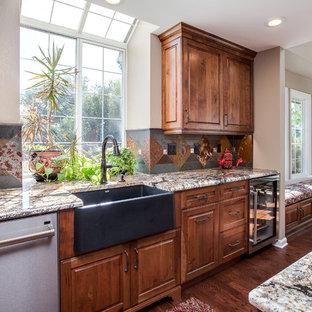 デンバーの大きいラスティックスタイルのおしゃれなキッチン (エプロンフロントシンク、レイズドパネル扉のキャビネット、中間色木目調キャビネット、御影石カウンター、マルチカラーのキッチンパネル、テラコッタタイルのキッチンパネル、シルバーの調理設備の、無垢フローリング、茶色い床、茶色いキッチンカウンター) の写真
