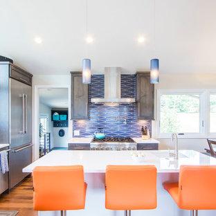 デンバーのトランジショナルスタイルのおしゃれなキッチン (アンダーカウンターシンク、シェーカースタイル扉のキャビネット、中間色木目調キャビネット、珪岩カウンター、青いキッチンパネル、シルバーの調理設備の、無垢フローリング、茶色い床、白いキッチンカウンター) の写真