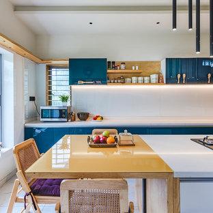 На фото: параллельные кухни в восточном стиле с обеденным столом, плоскими фасадами, синими фасадами, белым фартуком, фартуком из стекла, белым полом и желтой столешницей