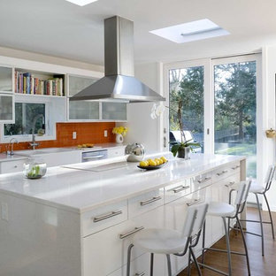 Photo of a contemporary galley kitchen in New York with a farmhouse sink, glass-front cabinets, white cabinets, quartz benchtops, orange splashback, stainless steel appliances and glass tile splashback.