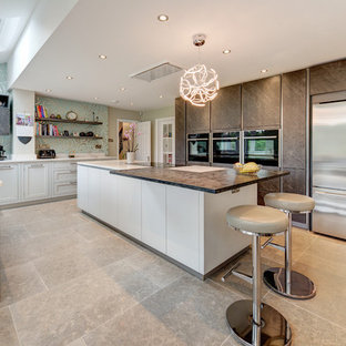 Design ideas for a large contemporary u-shaped kitchen in London with a submerged sink, flat-panel cabinets, brown cabinets, stainless steel appliances, an island, grey floors and brown worktops.