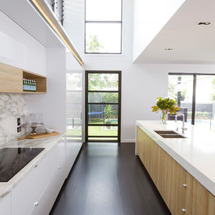 This is an example of a large contemporary galley kitchen in Brisbane with dark hardwood floors, with island, flat-panel cabinets, white cabinets, grey splashback, brown floor and white benchtop.