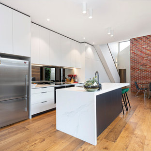 Contemporary eat-in kitchen in Melbourne with an undermount sink, white cabinets, quartz benchtops, grey splashback, mirror splashback, stainless steel appliances, light hardwood floors, with island and white benchtop.