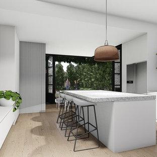Foto de cocina comedor en L, actual, pequeña, con puertas de armario blancas, encimera de terrazo, electrodomésticos de acero inoxidable, suelo de madera en tonos medios, una isla y encimeras blancas